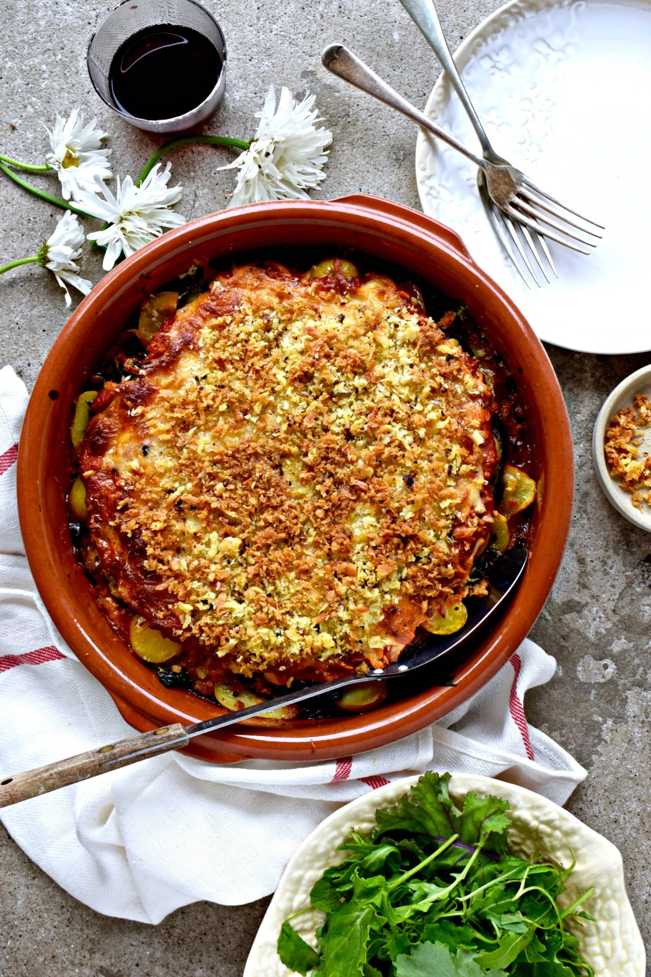 A delicious late-summer jackpot of a recipe,done alla parmigiana. Not just eggplants, but chard, potatoes, garlicky oil and a simple homemade sauce, layered up and covered in gooey cheese and earthy porcini breadcrumbs. Hearty yet light; a vegetarian recipe the whole family will love.