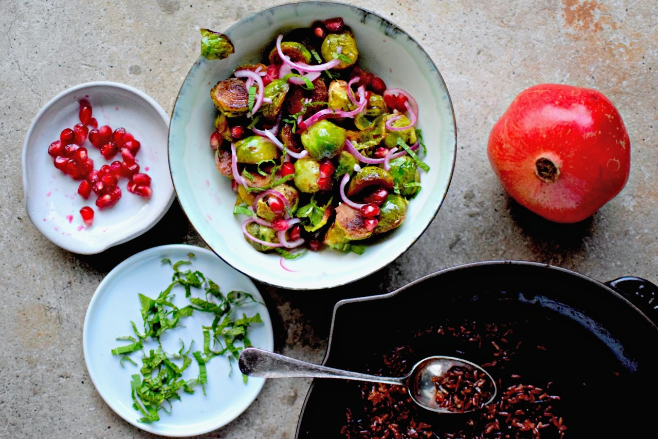 Pan-fried Brussels sprouts with tangy pomegranate molasses, mint, pickled red onion and crispy red & wild rice: because side dishes don't need to be boring. Perfect for the festive table, or as a perky midweek addition to a meal. A vegan and anti-inflammatory recipe.